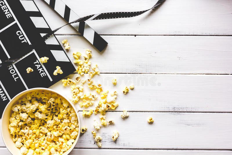 Watching movie with popcorn on wooden background top view.  royalty free stock image