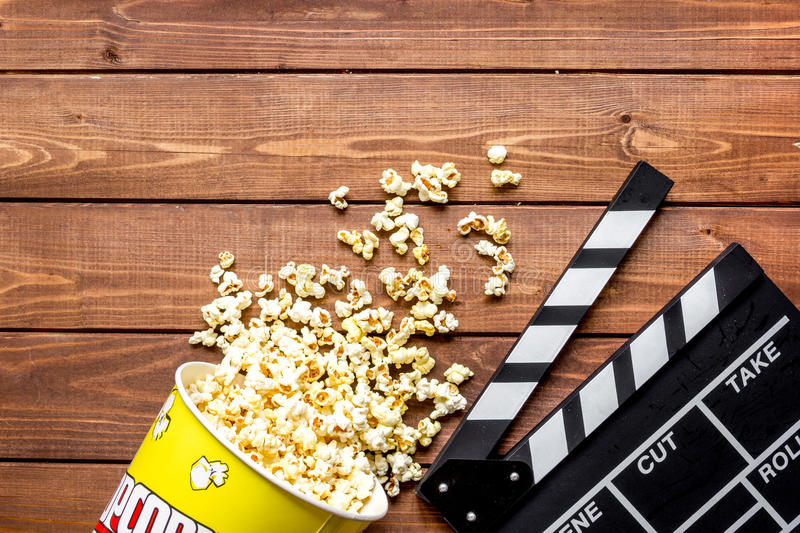 Watching movie with popcorn on wooden background top view.  stock images