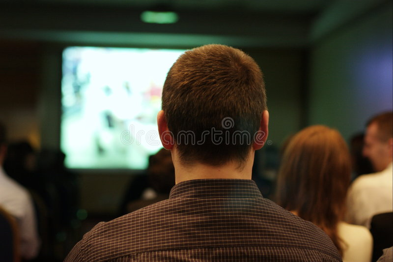 Watching movies. Man and other people sitting in movies watching film on screen, shown from rear royalty free stock photography