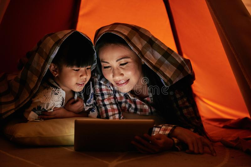 Watching movies. Mother and daughter under the blanket watching movies online stock photography