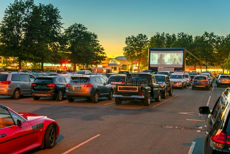 Watching movies in the open air in a car park in the city in the. Watching movies in the open air in a car park in the city in warm summer evening royalty free stock images