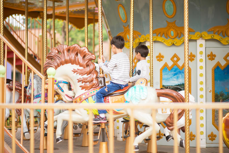 Watching my kids on mary go round. Little boy playing in mary go round at fun park royalty free stock photography