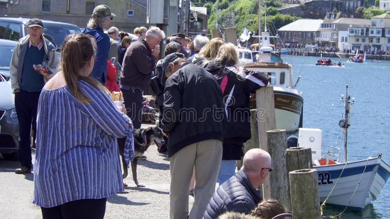 Watching from the quayside at the raft race Looe Cornwall stock images