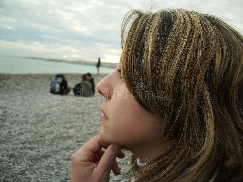 Watching the sea. A girl watching the sea and thinking stock photos