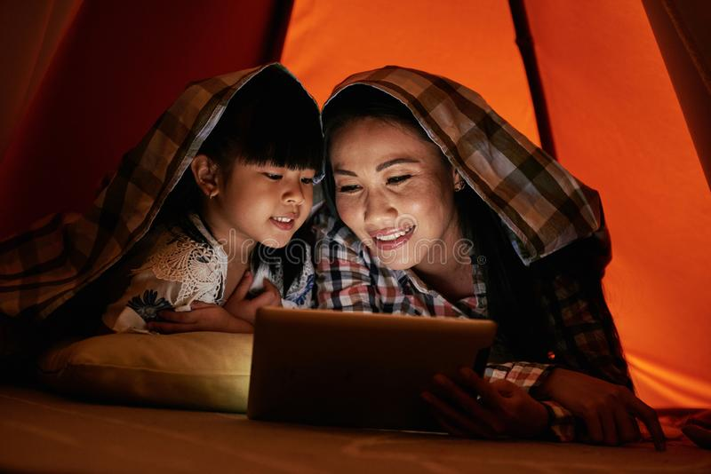 Watching shows at night. Asian women and her daughter lying under blanket and watching shows online stock images