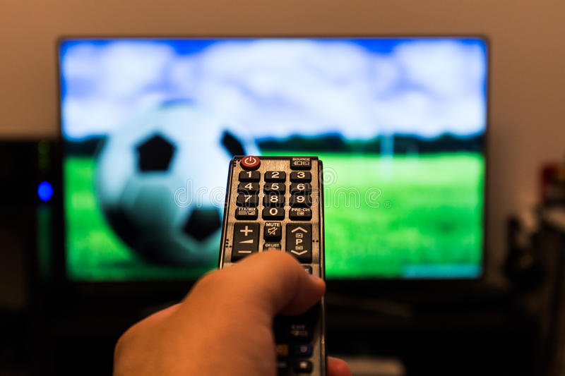 Watching soccer / football game on modern tv, with a close-up of. The remote control royalty free stock image