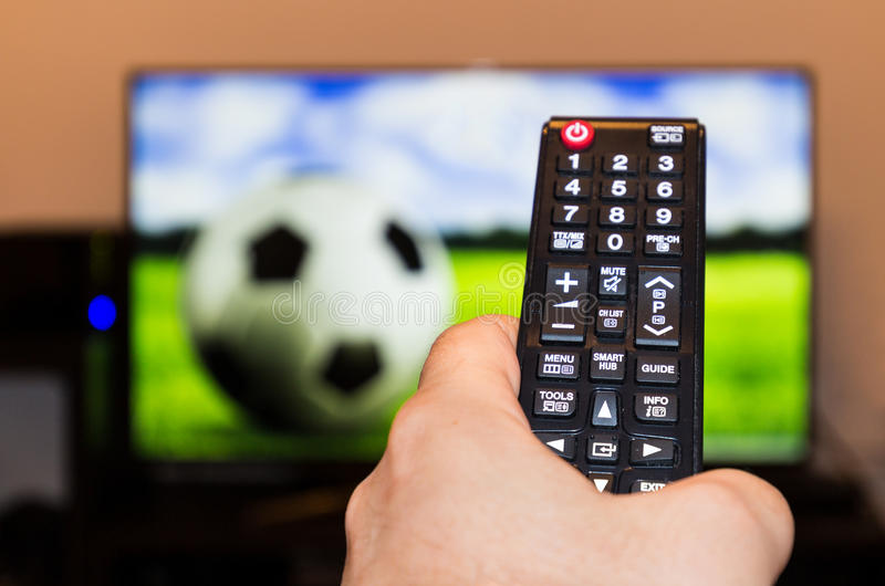 Watching soccer / football game on modern tv, with a close-up of. The remote control stock images