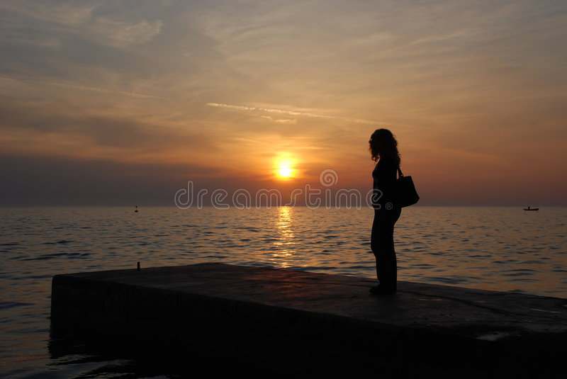 Watching the sunset. Female silhouette with long hair and bag watching sunset from dock - Pirano, Slovenia royalty free stock image