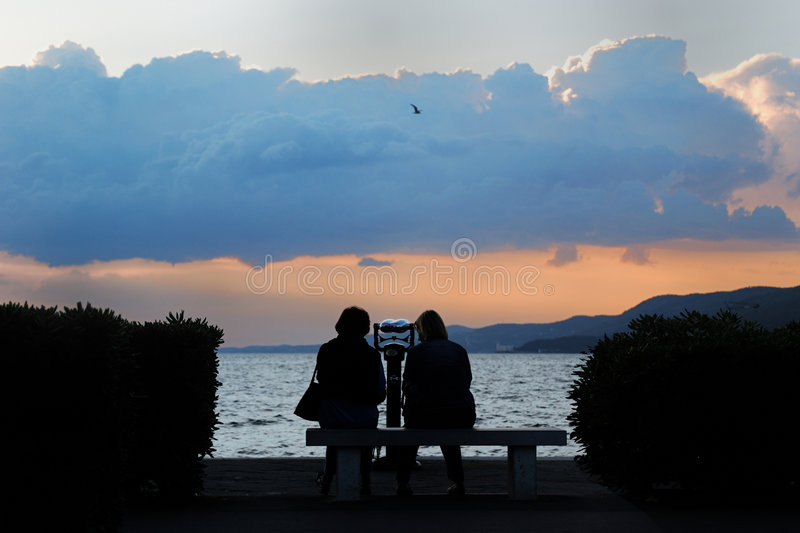Watching the sunset. Two people watching the storm arriving during sunset, mountains in the background - Trieste, Italy stock image