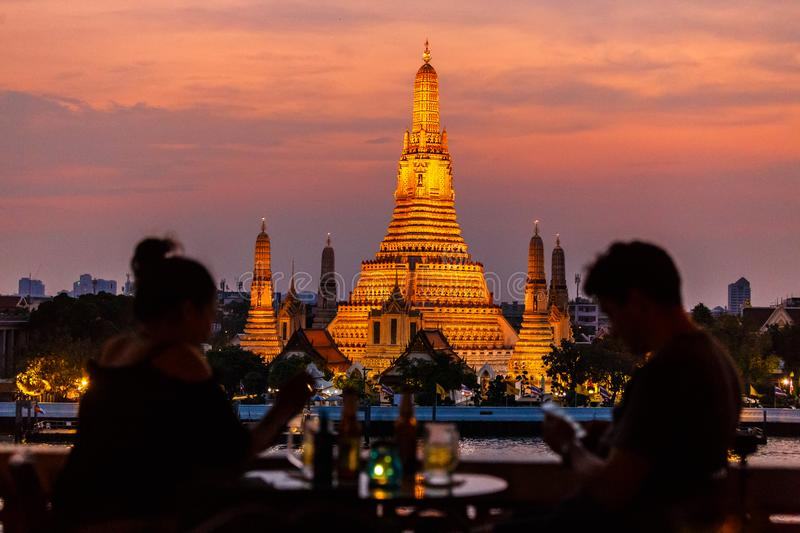 Watching the sunset at Wat Arun from Amorosa Bar. On the other side of the river. Wat Arun or the Temple of Dawn is a buddhist temple on the banks of Chao stock image