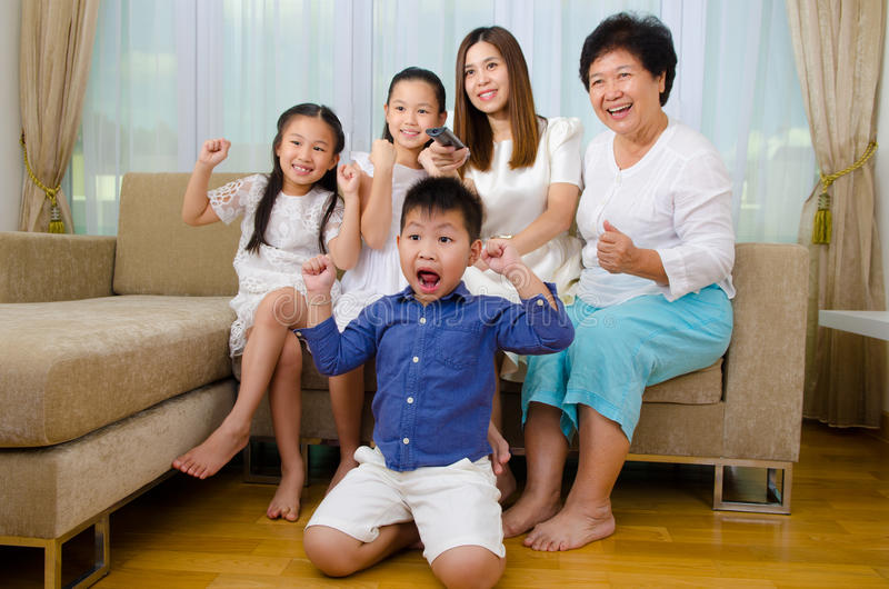Watching television. Asian three generations family watching television and shouting on their home side in a sporting competition royalty free stock photo