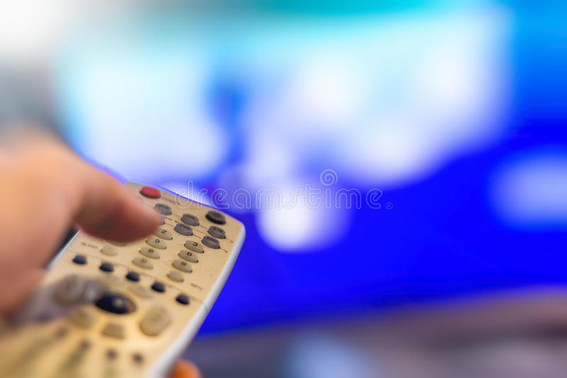 Watching Television. Close up of remote in hand with shallow depth of field during television watching stock photo