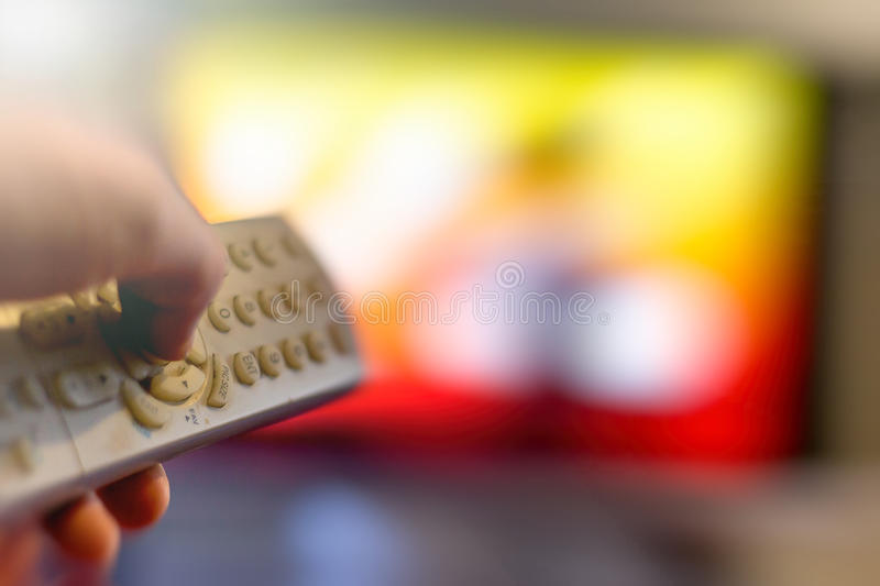 Watching Television. Close up of remote in hand with shallow depth of field during television watching royalty free stock photography