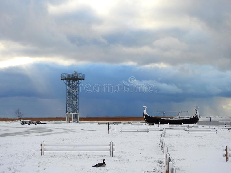 Watching tower, ship and bird near Curonian spit, Lithuania. High metallic watching tower, old wooden ship and beautiful goose bird on Curonian spit shore in stock photography