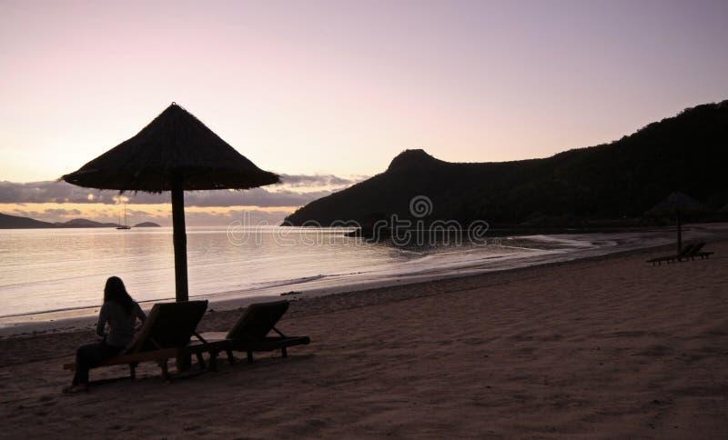 Watching a tropical island sunrise stock image