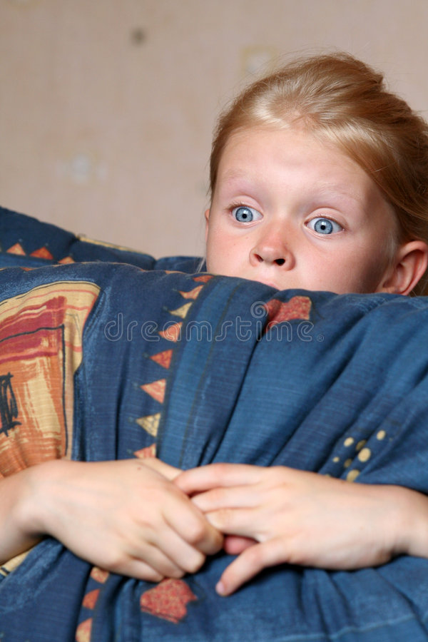 Watching TV. Little girl looking at something frightening stock photos