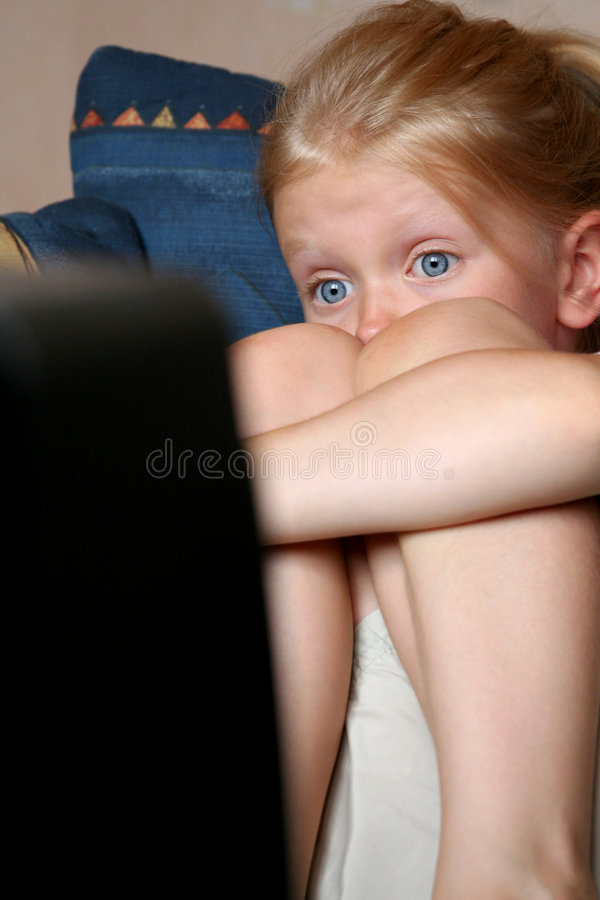 Watching TV. Little girl looking at something frightening stock photography