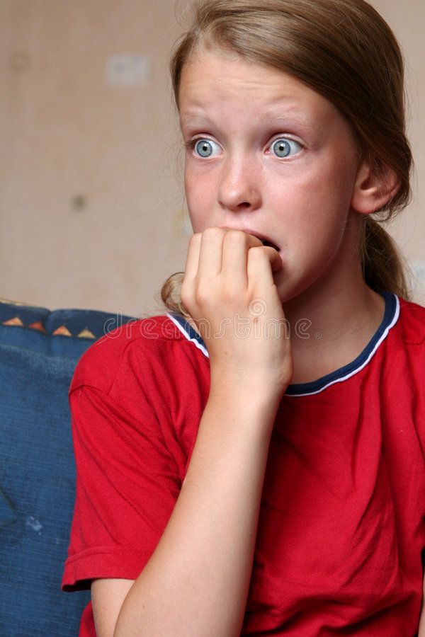 Watching TV. Young girl looking at something frightening royalty free stock image