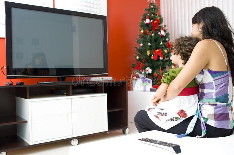 Watching TV. Adult Woman and Child Watching TV