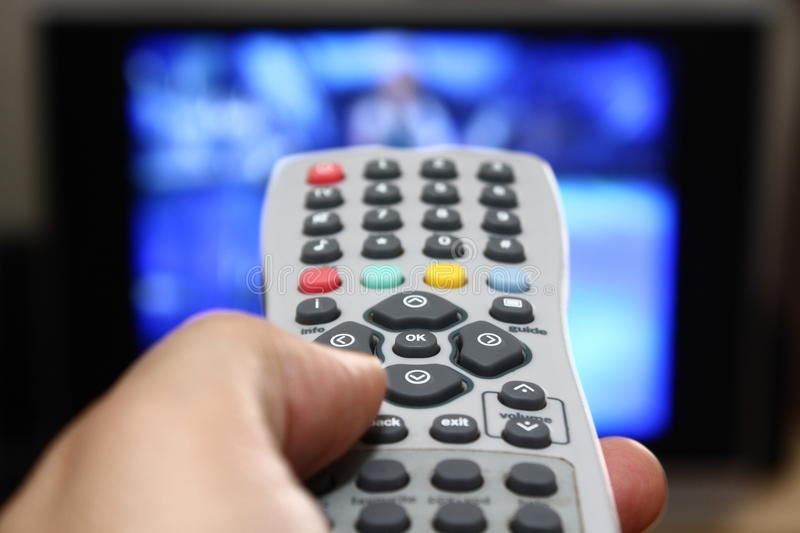 Watching TV. A left hand handling a TV remote control changing channels while watching TV in background