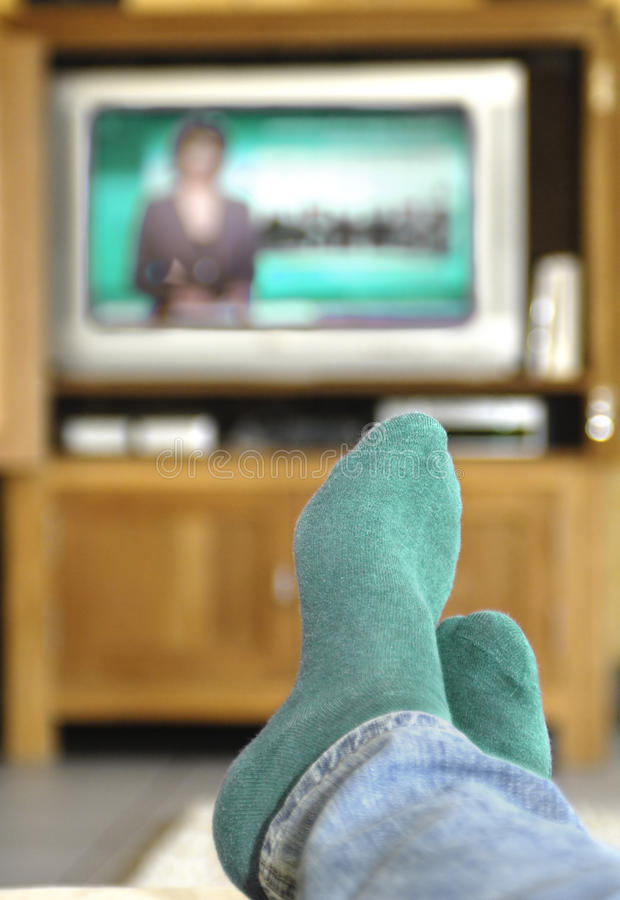 Watching TV. Feet in socks in front of an television stock photography