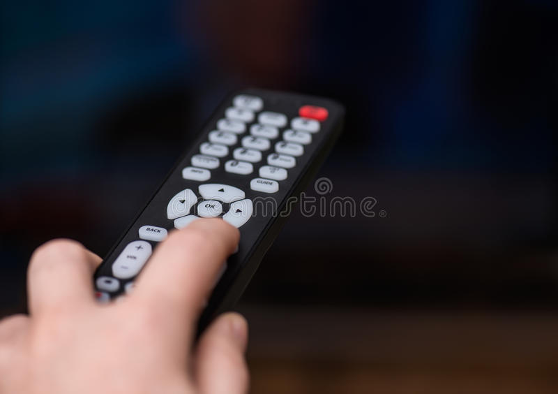Watching TV and using remote controller. Hand holds remote , buttons stock photos