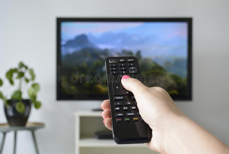 Watching TV. A woman`s hand holding the TV remote control with a television in the background stock photo