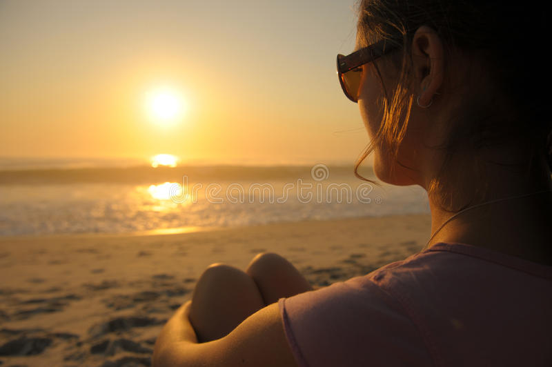 Watching the waves. Girl watches the waves roll in as the sun rises on the day royalty free stock photos