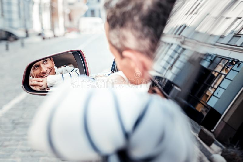 Joyful man looking for his friend. Watching you. Positive delighted male person sitting in his car and keeping smile on his face while leaning on door stock photos