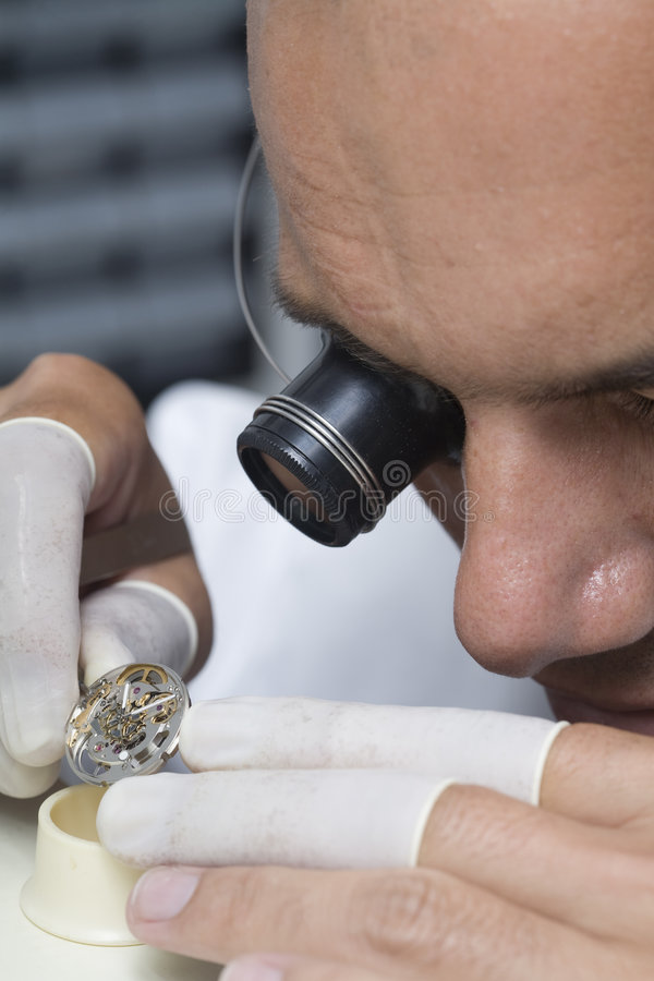Watchmaker. A watchmaker or repair man in action, viewing very closely a swiss watch royalty free stock photo