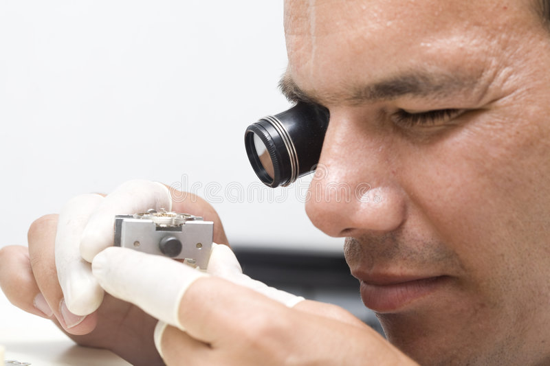 Watchmaker. A watchmaker or repair man in action, viewing very closely a swiss watch royalty free stock photos