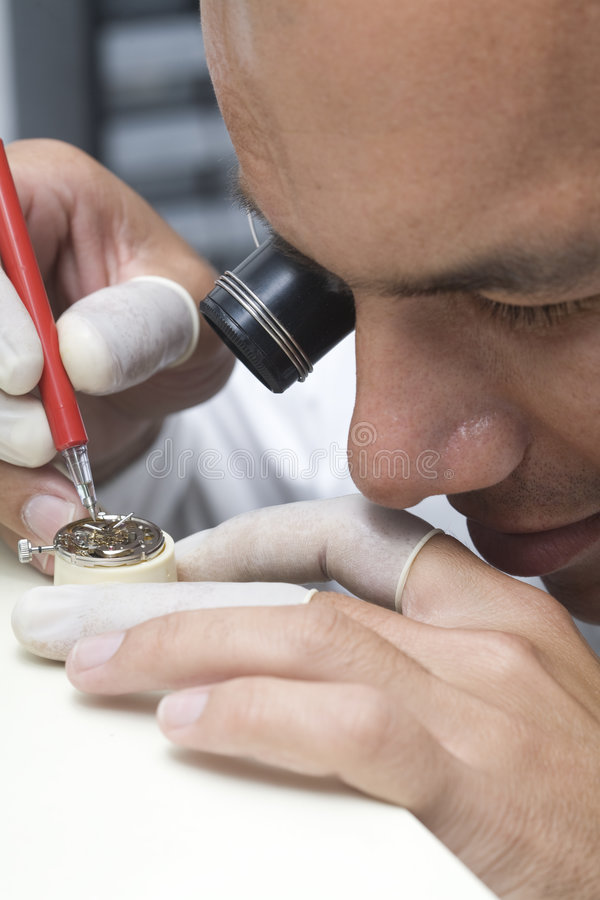 Watchmaker. A watchmaker or repair man in action, viewing very closely a swiss watch royalty free stock images