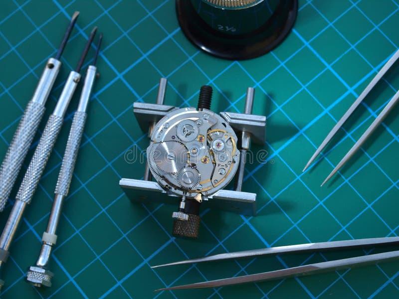 Repairing old watch. Watchmaker desktop: vintage watch mechanism under repair  and several horology tools over desktop royalty free stock photos