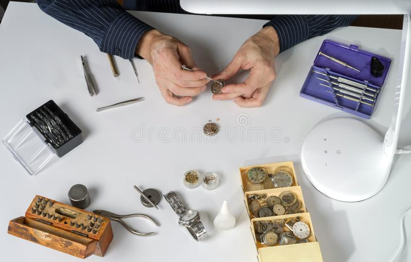 The watchmaker is repairing the mechanical watch. Workplace of the clockmaker for the repair of mechanical watches royalty free stock images