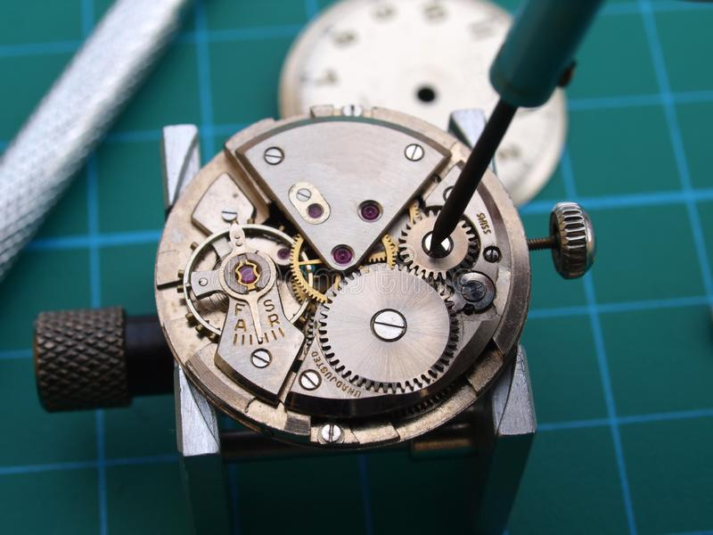 Watchmaker repairing old mechanical watch. Close up of watchmaker repairing old mechanical watch caliber royalty free stock images