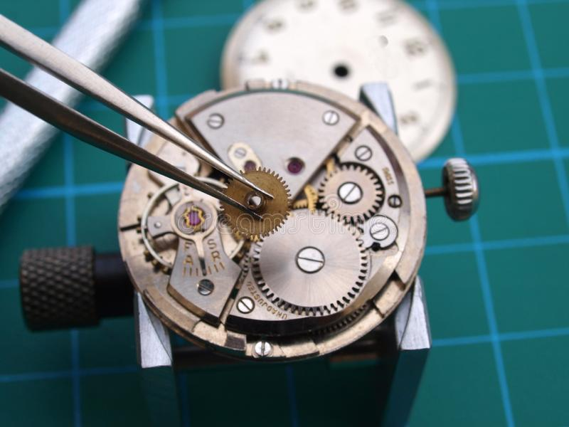 Watchmaker repairing old mechanical watch. Close up of watchmaker repairing old mechanical watch caliber taking small gear with tweezers stock photography