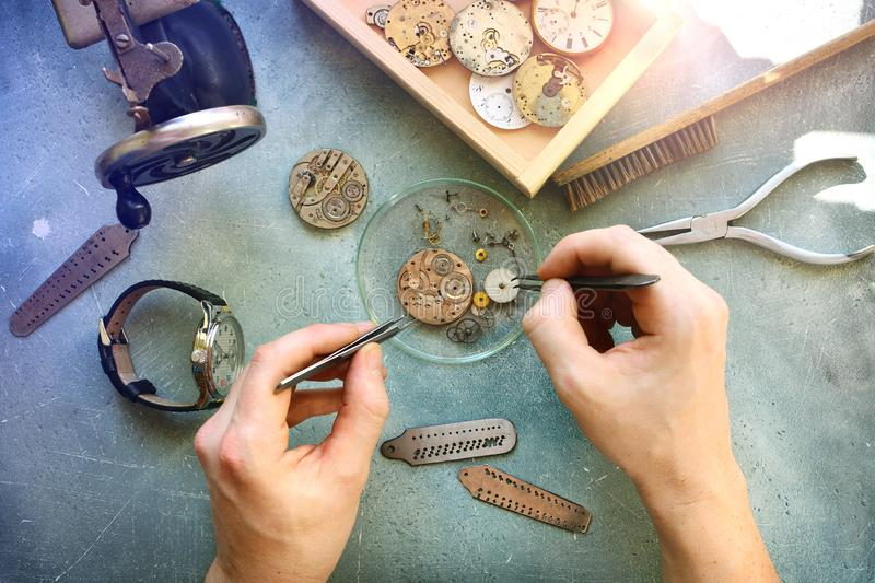 Watchmaker at work in workshop. Flat lay. Workplace of watch repairer. Process of repair mechanical watches. stock image