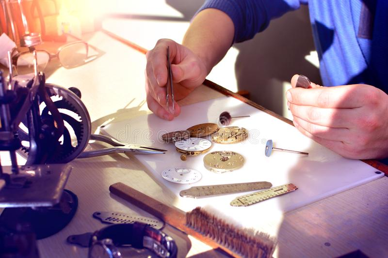 Watchmaker at work in workshop. Workplace of watch repairer. Process of repair mechanical watches. stock images