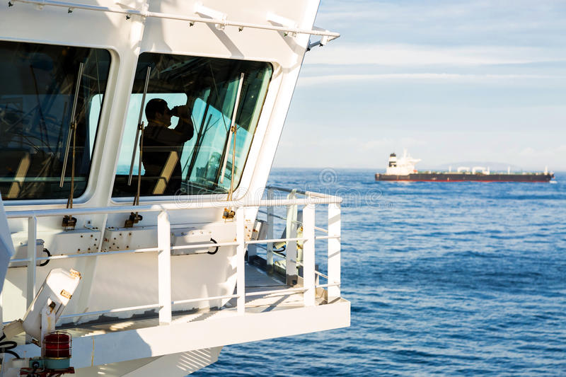 Watchman on the navigation bridge. Watchman on the navigating bridge of a big tanker with another big ship on background royalty free stock image