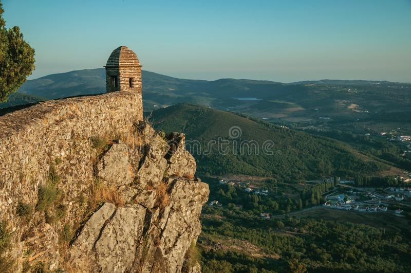 Watchtower made of bricks over cliff in Marvao. Small watchtower and stone wall over rocky cliff, with hilly landscape covered by trees on sunset at Marvao. An royalty free stock photo