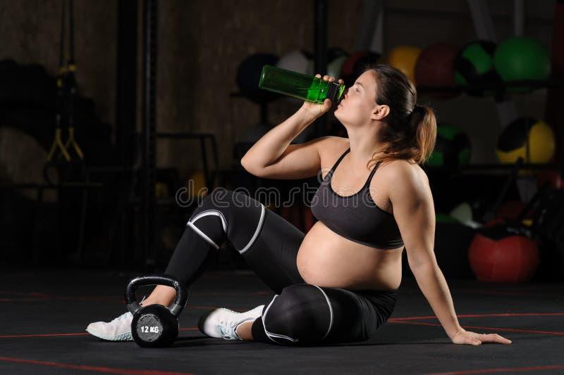 Wate молодой беременной женщины выпивая от пластиковой бутылки в спортзале стоковые фотографии rf