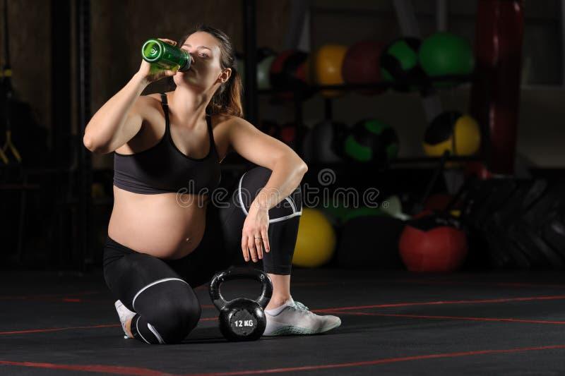 Wate de consumición joven de la mujer embarazada de la botella plástica en el gimnasio imagen de archivo libre de regalías