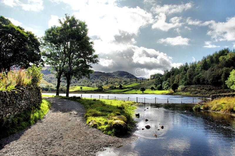 Sunny Watendlath Tarn and Beck in Cumbria. Watendlath Tarn in the Lakes District of Cumbria, England, United Kingdom. Water from the tarn flows into Watendlath stock image