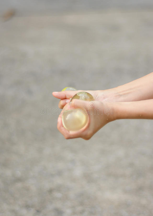 Water balloon. Girl hand holding water balloon at outdoor background royalty free stock image
