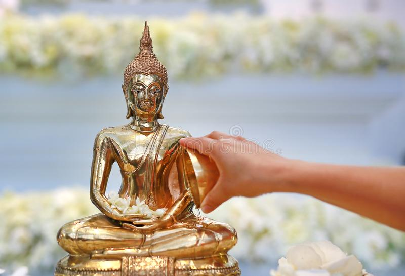 Water blessing ceremony for Songkran Festival or Thai New Year. People paying respects to a statue of Buddha by pouring water onto royalty free stock images