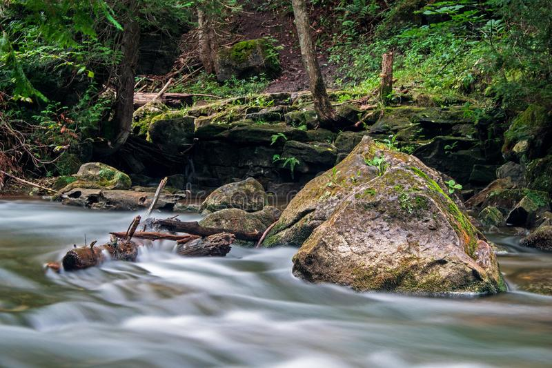 Water Blur Scene On The Boyne River. A moss covered rock sits solid in the fast moving waters of the Boyne River, just upstream from Hoggs Falls. The location is stock photo