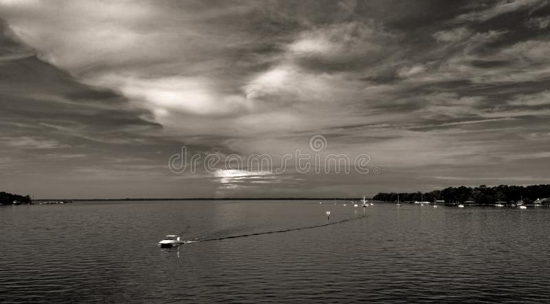 Water and boat with dramatic sky and clouds royalty free stock images