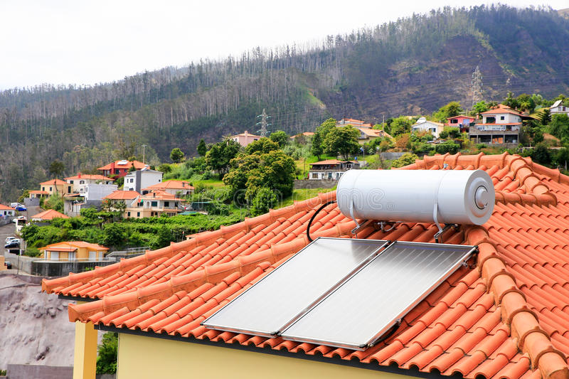 Water boiler with solar panels on roof of house. In village of Madeira stock photography
