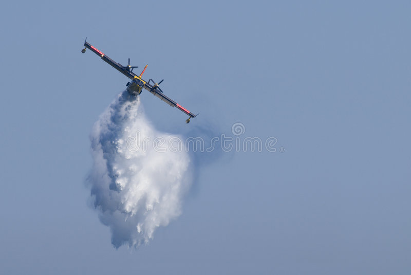 Water Bomber. A twin-engined water bomber dumping its load on a forest fire royalty free stock photo