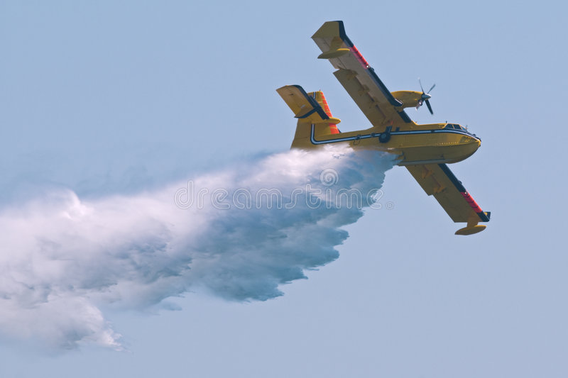 Water Bomber. A twin-engined water bomber dumping its load on a forest fire stock image